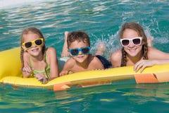 Trzy szczęśliwego dziecka bawić się na pływackim basenie przy dniem Tim Zdjęcie Stock
