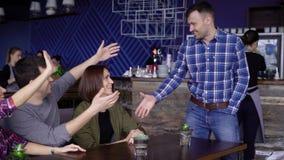Trzy szczęśliwego przyjaciela siedzą wpólnie przy powitaniem i restauracją ich przyjeżdżający męski członek trząść jego firma zbiory wideo