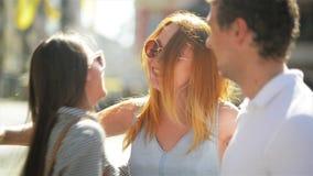 Trzy szczęśliwego przyjaciela spotyka w chodniczku ulica duży miasto Dwa dziewczyny i jeden chłopiec przytulenie na miastowym tle zbiory wideo