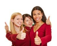 Trzy szczęśliwej dziewczyny trzyma aprobaty obrazy stock