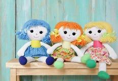 Trzy szczęśliwej gałganianej lali na drewnianym tle Fotografia Stock