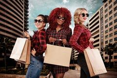 Trzy szczęśliwej kobiety w okularach przeciwsłonecznych Afro amerykanin, azjata i caucasian rasy, Robić zakupy na czarnym Piątku  zdjęcie stock