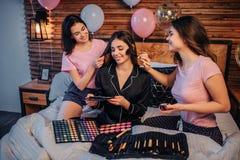 Trzy szczęśliwej młodej kobiety siedzą na łóżku w świątecznym pokoju Dwa dziewczyny robią haircare i makeup dla trzeci jeden Tam  zdjęcia royalty free