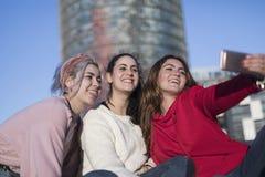 Trzy szczęśliwej najlepszy dziewczyny outdoors robi selfie na smartphon zdjęcia stock