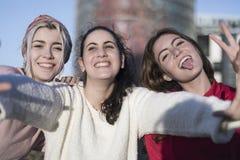 Trzy szczęśliwej najlepszy dziewczyny outdoors robi selfie na smartphon obraz stock
