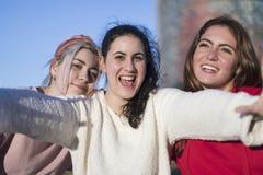 Trzy szczęśliwej najlepszy dziewczyny outdoors robi selfie na smartphon obrazy stock