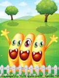 Trzy szczęśliwy pomarańczowy potwór blisko ogrodzenia ilustracji