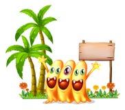 Trzy szczęśliwy pomarańczowy potwór przed pustym drewnianym signage Zdjęcia Stock