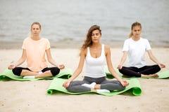 Trzy szczup?ej m?odej dziewczyny siedz? w joga pozy z przymkni?? oczami na matach na piaskowatej pla?y obok rzeki na ciep?ym dniu zdjęcie stock