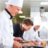 Trzy szef kuchni w drużynie w hotelowej lub restauracyjnej kuchni Zdjęcia Stock