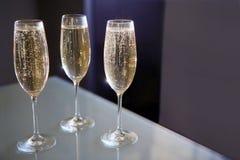 Trzy szkła szampan przy stołem Fotografia Stock