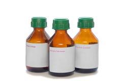 Trzy szklanej buteleczki z etykietką odizolowywającą na bielu Obraz Stock
