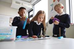 Trzy szkoły podstawowej dziecka pracuje wraz z zabawkarskimi budowa blokami w sali lekcyjnej dziewczyn czytelnicze instrukcje od  zdjęcie stock