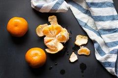 Trzy tangerines kłamają na czarnym stole z pasiastym bieliźnianym ręcznikiem Obraz Stock