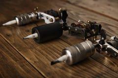 Trzy tatuażu pistoletu układali na brown drewnianym stole Obrazy Royalty Free