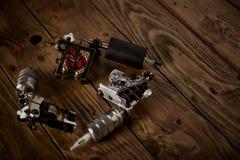 Trzy tatuażu pistoletu układali na brown drewnianym stole Obraz Royalty Free