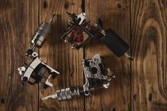 Trzy tatuażu pistoletu układali na brown drewnianym stole Zdjęcia Stock