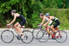 Trzy tiathletes przejażdżki prędkości cyklu podczas triathlon rywalizaci Obrazy Royalty Free