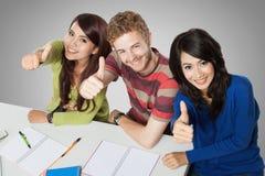 Trzy uśmiechniętego ucznia studiuje wpólnie zdjęcie royalty free
