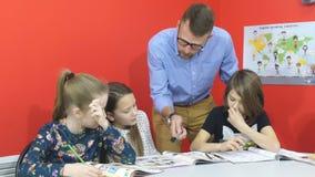 Trzy uczennicy słuchają nauczyciel na lekci zbiory