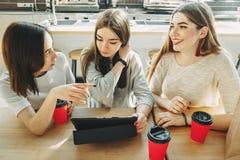 Trzy ucznia dyskutuje projekt używać pastylkę obrazy royalty free