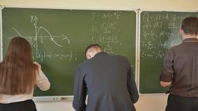 Trzy ucznia piszą na blackboard matematycznie formułach w sala lekcyjnej Rosjanin szkoła zdjęcie wideo