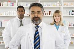 Trzy Ufnej farmaceuty Stoi Przy apteką Zdjęcia Royalty Free
