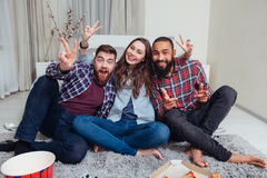 Trzy uśmiechniętego przyjaciela siedzi w pokoju i pokazuje zwycięstwo znaka Obrazy Stock