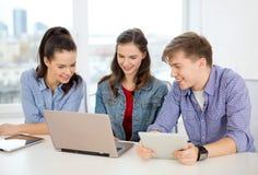 Trzy uśmiechniętego ucznia z laptopu i pastylki komputerem osobistym Obrazy Stock