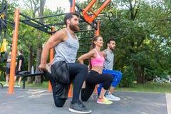 Trzy ustalali przyjaciół robi rozciągań ćwiczeniom dla nóg jak zdjęcia royalty free