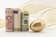 Trzy ważnej waluty z złocistym jajkiem Fotografia Royalty Free