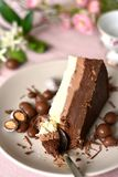 Trzy warstwy czekoladowy śmietanka tort, plasterek na talerzu, łyżka bierze kawałek fotografia royalty free