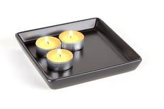 Trzy świeczki na czarnym talerzu Obraz Stock
