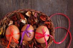Trzy Wielkanocnego jajka są dekorujący jaskrawi z kolor taśmami w koszu z suchymi kwiatami Zdjęcie Stock