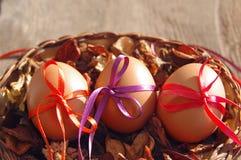 Trzy Wielkanocnego jajka są dekorujący jaskrawi z kolor taśmami w koszu z suchymi kwiatami Zdjęcia Stock
