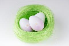 Trzy Wielkanocnego jajka w okrąg zieleni gniazdeczku Zdjęcie Stock