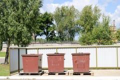 Trzy wielki przemysłowy brown kosz na śmiecie, grat dla oddzielnej śmieciarskiej kolekci w przemysłowej roślinie obraz royalty free