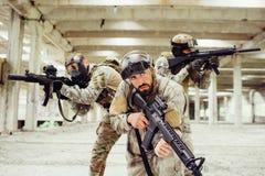 Trzy wojownika pozują Dwa one są przyglądający różne strony i brać przez karabinowego Lenz cel podczas gdy mężczyzna wewnątrz Obrazy Royalty Free