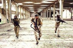 Trzy wojownika z wyposażeniem biegają w dół jaskrawego i dużego pokój Dwa one są przyglądający strony podczas gdy mężczyzna wewną Fotografia Stock