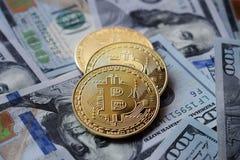 Trzy złota Bitcoin monety na USA dolarach fotografia stock