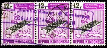 Trzy znaczka pocztowego drukującego w Indonezja pokazują instrumenty muzycznych, seria, około 1967 obraz stock