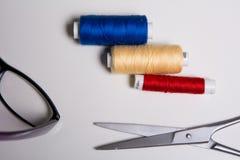 Trzy zwitki stubarwne nici, szkła i nożyce, obrazy stock