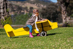 Trzyletnia dziewczyna na kolor żółty zabawki samolocie outdoors Fotografia Stock