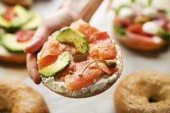 Trzymać Zdrowego Bagel z uwędzonym łososiem i avocado fotografia royalty free