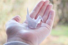 Trzymać małego papierowego żurawia w ręce Fotografia Stock