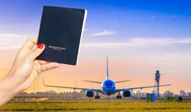 Trzymać rodzajowego paszport z jeden z ostrość samolotu taxiing przy zmierzchem Zdjęcie Royalty Free