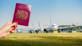 Trzymać UK paszport z rzędem samolotów taxiing Zdjęcie Stock