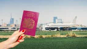 Trzymać UK paszport z rodzajowy samolotowy taxiing Fotografia Stock