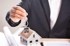 Trzymający dom i kluczowego proponowanie mieści nabycie lub wynajem zdjęcie royalty free