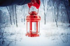 Trzymający czerwoną świeczkę latarniowa w zima lesie Zdjęcie Royalty Free